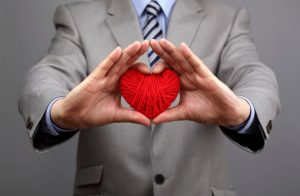A businessman holds out a red heart