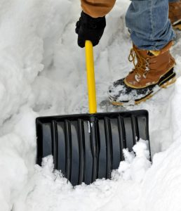 A person shovels away snow to protect their driveway.